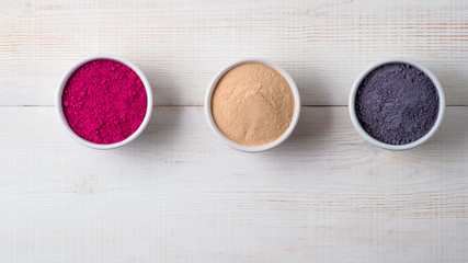 Set of superfoods in white bowls on wooden background.