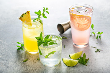 Refreshing summer cocktails on the table with lime, grapefruit and pineapple