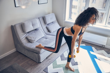 Serious slim girl with dumbbells at home