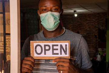 a local african business owner holding open sign standing in front of door