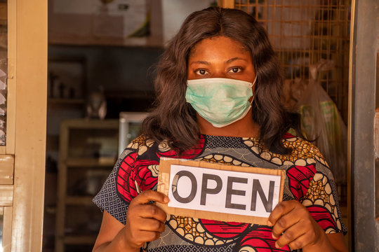 local african business owner holding a open sign in her store