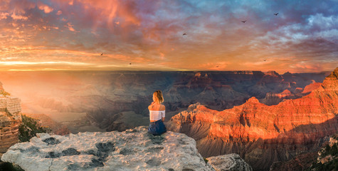 Young woman sitting on the edge of rim and enjoying the panoramic view of Grand Canyon