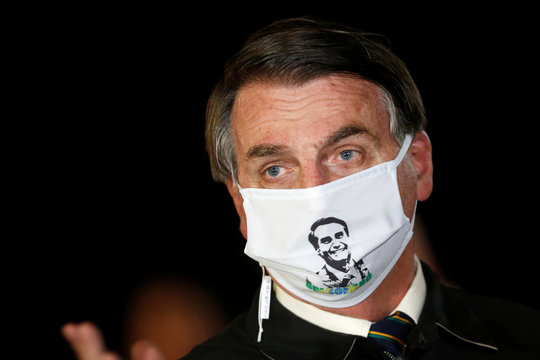 Brazil's President Jair Bolsonaro speaks with journalists while wearing a protective face mask as he arrives at Alvorada Palace, amid the coronavirus disease (COVID-19) outbreak, in Brasilia
