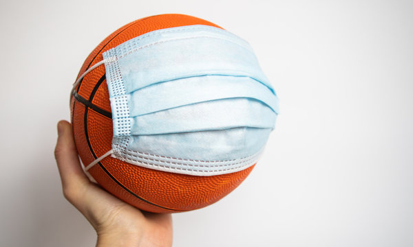 hand holding a basketball with  medical mask sports after the covid pandemic concept