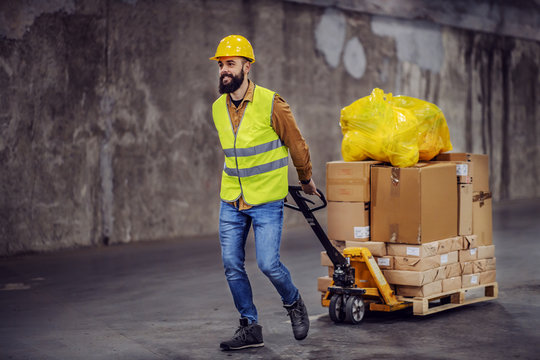 Full length of smiling hardworking bearded worker in vest, with safety helmet on head pulling a pallet truck with boxes, sack and building material. Building in construction process interior.