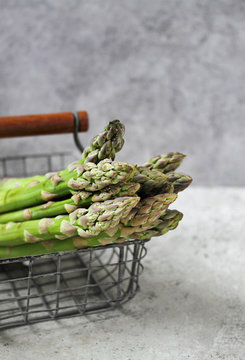 Banches of fresh green asparagus in an iron basket on a concrete background.