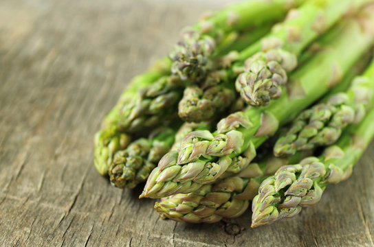 Banches of fresh green asparagus on a wooden background. Healty food