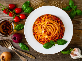 Spaghetti with tomato sauce, meat and parmesan on wooden background