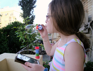Funny lovely girl blowing soap bubbles from the balcony with smartphone