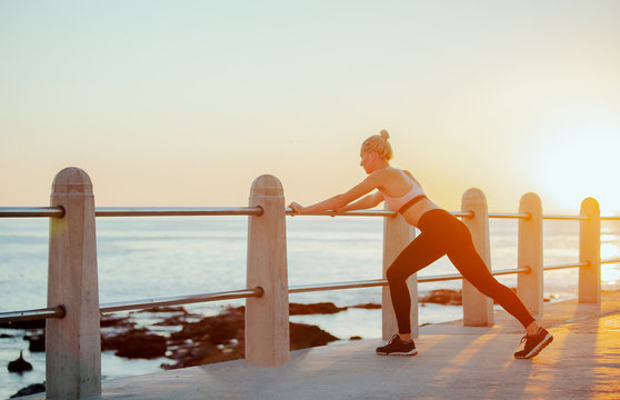 Beautiful woman stretching hamstring against balustrade during sunset