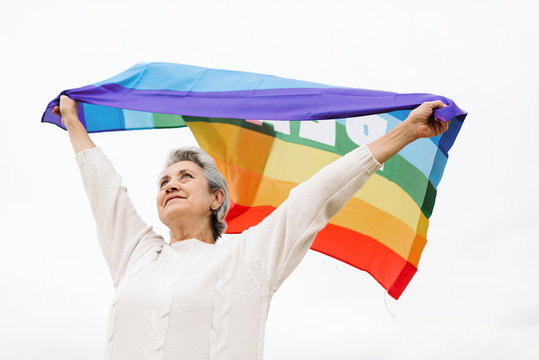Low angle view of a old woman holding waving LGBT flag over head.  LGBT concept and old age.  white background