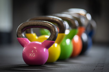 Row of colorful kettlebell weights in the gym