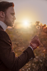 young businessman blowing dandelion in sunset