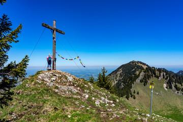 Voralpenland Chiemgau: Wanderer am Feichteck mit Blick auf den Hochries Gipfel