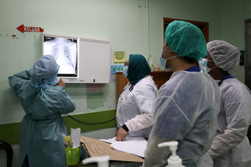 Health workers look at x-rays of a patient at Emergency Department in the Kuala Lumpur Hospital, amid the coronavirus disease (COVID-19) outbreak, in Kuala Lumpur