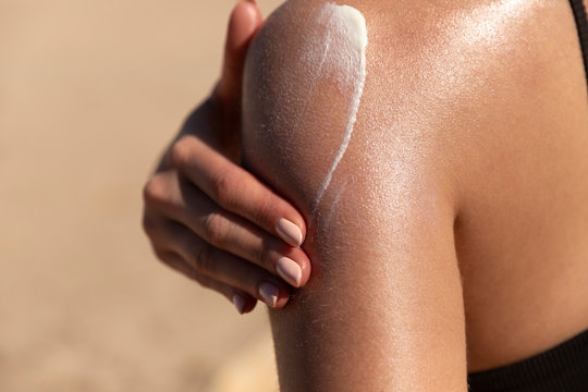 Young woman applying sun cream or sunscreen on her tanned shoulder to protect her skin from the sun. Shot on a sunny day with blurry sand in the background