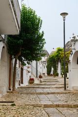 traditional white houses, called trulli, in street of  Unesco town Alberobello, Italy
