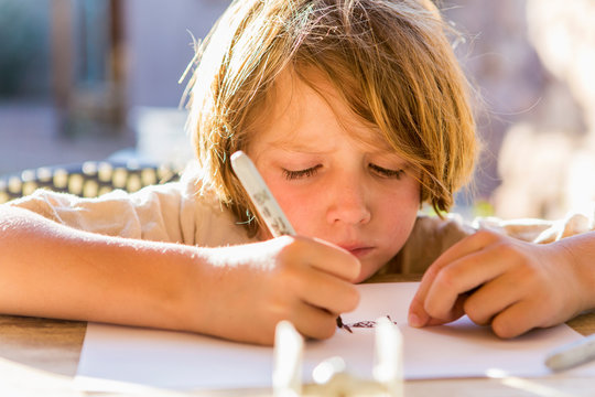 6 year old boy drawing on paper with a marker at sunset