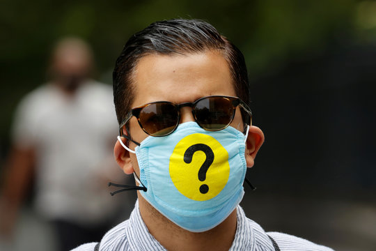 Man wears a protective face mask decorated with a question mark during outbreak of the coronavirus disease (COVID-19) in New York