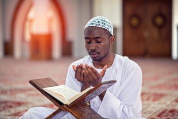 Religious black muslim man praying inside the mosque