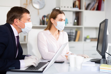 Entrepreneur in medical mask working with female coworker in office