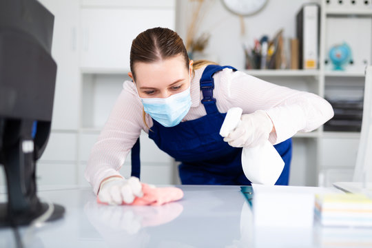 Woman professional cleaner in protective medical mask cleaning desk in office