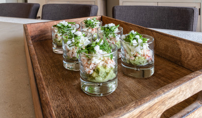 Festive appetizer glasses with avocado mousse and North Sea crab on a wooden tray.