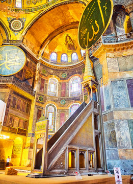 Istanbul, Turkey - July 10, 2018. Minbar, the pulpit at right hand side of the altar of Hagia Sophia mosque, and the Apse with the mosaic of the Virgin Mary in the background.