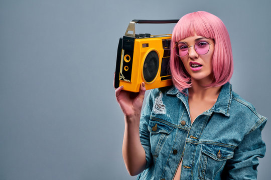 Confident young woman with pink hair and sunglasses posing with yellow old boombox in a shoulder isolated on grey wall background studio portrait.