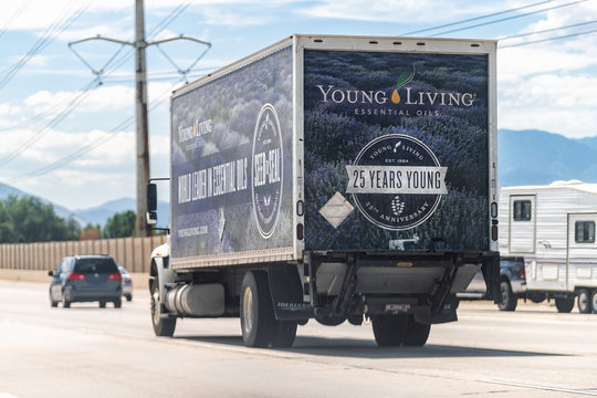 American Fork, USA - July 29, 2019: Young Living Essential Oils business company delivery truck sign near warehouse on highway road in Utah cars in traffic