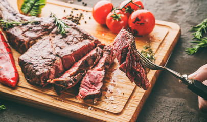 Deurstickers Steakhouse Hands cut grilled tomahawk meat medium rare or rib eye steak on wooden cutting board with grilled vegetables on dark background, close up, toning