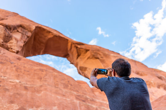 Arches National Park canyons with Skyline Arch in background and young man standing taking picture of view with phone on trail hike in Utah, USA