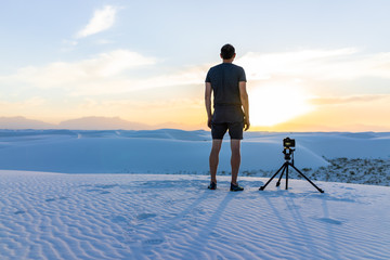 Young man professional photographer with camera tripod filming time lapse photography at White sands dunes national monument, New Mexico at sunset with Organ mountains view Fotobehang
