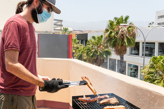 Man is barbequing in the terrace with a mask due covid 19