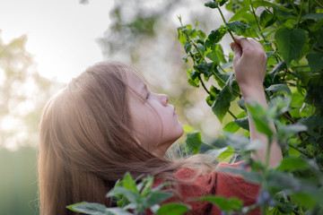 Cute little girl exploring nature by watching for bugs on a jasmine bush. Portrait of a beautiful girl with long curly hair. Wall mural