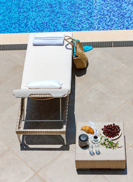 sun loungers, table with fruit, coffee and croissant near the outdoor pool.