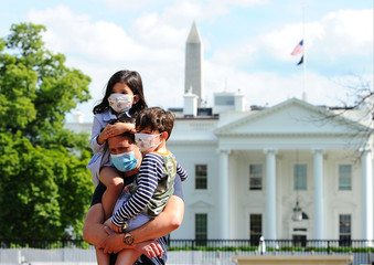 Jason Aguirre carries his children, Elle, 4, and Shai, 6, after viewing the White House, where flags fly at half-staff to commemorate the victims of the coronavirus disease (COVID-19), in Washington