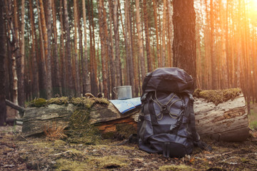 Tourist backpack, metal mug and map in the forest. Concept of a hiking trip to the forest or mountains