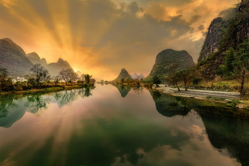 Dramatic shot of the sun rising behind limestone karst mountains in Yangshuo County with the scene reflected in the river