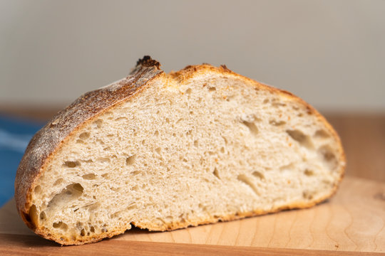 Homemade boule (round loaf) of freshly baked sourdough bread on a wood cutting board