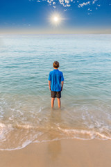 Young boy staring our towards to the horizon with his feet in the surf and a beautiful blue sea and a dramatic sky with a sun star in the distance.