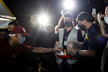 Brazil's President Jair Bolsonaro buy a hotdog in a street cafeteria, amid the coronavirus disease (COVID-19) outbreak, in Brasilia