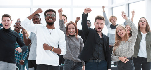 group of happy young people standing with their hands up