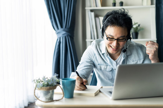 Asian businessman talking to colleague team in video call conference feeling glad, happy with smile face. Man using computer laptop and headphone for online meeting. Smart working from home concept.