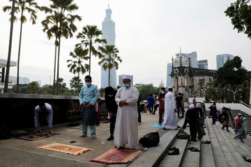 Muslims disperse after they were warned by police officers outside the closed National Mosque while celebrating Eid al-Fitr amid the coronavirus disease (COVID-19) outbreak in Kuala Lumpur