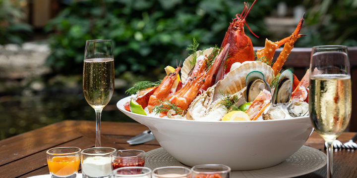 Bowl of gourmet fresh seafood on ice with savory sauce serve with white wine glass on vintage wooden table. Restaurant gastronomy food and drink consumerism concept.