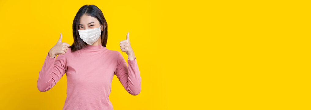 Asian smiling woman wearing mask and thumb up action to be grad, banner or showing on isolated yellow color background