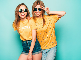 Two young beautiful smiling hipster girls in trendy summer yellow T-shirts. Sexy carefree women...