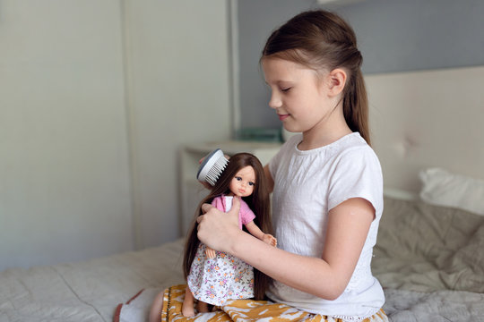 Caucasian girl combing a doll with long hair, a girl playing dolls. Traditional children's games for girls and childhood without gadgets.