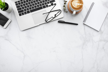 White marble office desk table with blank notebook, laptop computer, cup of coffee, smartphone and...